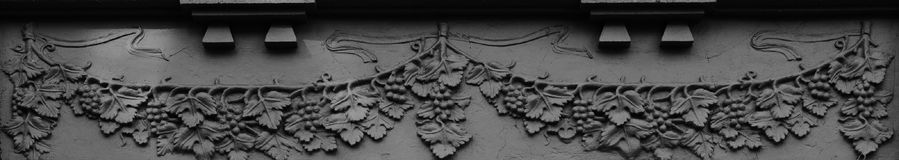 The grapes are ready to show. Shot in black and white, detail on the sculpture on the facade of this historic building representing some characters. Set in Logro Royalty Free Stock Photos