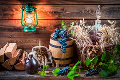 Grapes and red wine in a demijohn. On old wooden table Royalty Free Stock Photo