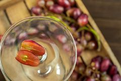 Grapes with seeds, cut in half close up and copy space. A large bunch of ripe grapes in a glass on the background of a dark textur. Ed wooden table stock images