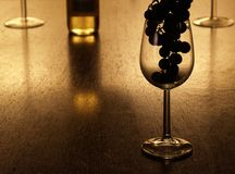 Grapes silhouette in a wineglass. Empty glass with a silhouette of grapes in it and a bottle of white wine in the background Royalty Free Stock Image