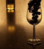 Grapes silhouette in a wineglass. Empty glass with a silhouette of grapes in it and a bottle of white wine in the background Royalty Free Stock Photos