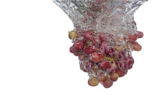 Grapes Splash. A Bunch Of Fresh Grapes Making A Splash Through Some Water On An Isolated Background royalty free stock image