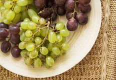 Grapes on straw table Royalty Free Stock Photography
