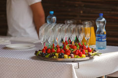 Grapes and strawberries lay on the plate behind empty wineglasse Royalty Free Stock Image