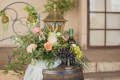 Grapes on vase near flowers and bottle of vine Royalty Free Stock Image