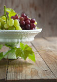 Grapes in vase on a wooden table Stock Images