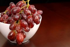 Grapes in a white bowl on table. Glistening grapes in a white bowl on table Royalty Free Stock Photography