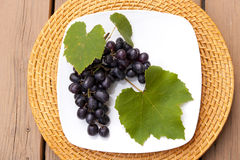 Grapes on white plate Stock Images