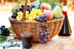 Grapes in wicker basket and red wine Royalty Free Stock Images