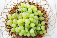 Grapes in a wicker plate. Bunch of grapes in a wicker plate on a white wooden background Royalty Free Stock Photo