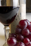 Grapes and wine. Grapes and red wine with a bottle and a cup Royalty Free Stock Image