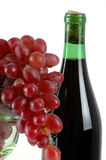 Grapes and Wine. Bunch of red grapes in a wine glass with a wine bottle Stock Image