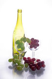 Grapes with wine bottle. Red and white grapes in wine glass in front of wine bottle royalty free stock images