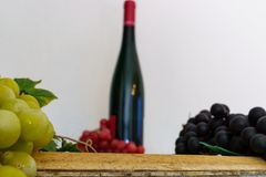 Grapes and a wine bottle on an oak barrel. Green grapes and a wine bottle on an old oak barrel stock image