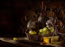 Grapes, wine and cheese in the wine cellar. Low key. royalty free stock photography
