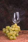 Grapes and wine glass. A bunch of grapes and an empty wine glass Royalty Free Stock Image