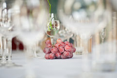 Grapes and wine glasses on the table. Celebration table decorated with grapes and wine glasses Royalty Free Stock Photos