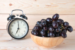 Grapes in wood bowl on table with seven o'clock background. Grapes in wood bowl on table Royalty Free Stock Photos