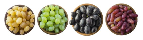 Grapes in a wooden bowl isolated on white background. Blue, yellow, red and green grapes on white background. Vegetarian or health stock image