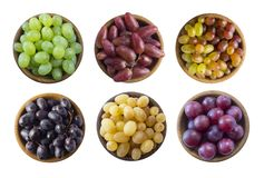 Grapes in a wooden bowl isolated on white background. Yellow, blue, pink and green grapes on white background. stock photo