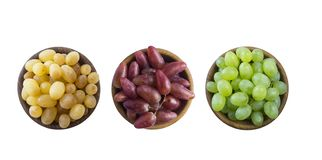 Grapes in a wooden bowl isolated on white background. Yellow, pink and green grapes on white background. royalty free stock image