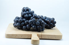 Grapes on a wooden plate Royalty Free Stock Photo