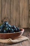 Grapes in  wooden plate. Grapes in a wooden plate on wood background Royalty Free Stock Image