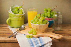 Grapes on wooden table. Still life composition with grapes and tableware. Royalty Free Stock Photos