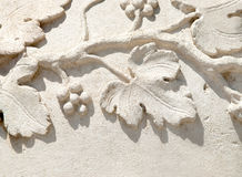 Grapevine bas-relif. Bas-relief on stone with stylized grapevine's fruits and leafs Stock Images
