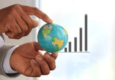 Graph. Image of a graph and a young businessman holding a globe Stock Image