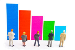 Graph. Miniature business figures standing in front of bars of colors Stock Photos