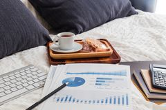 Graph analysis documents on bed with tea break. Royalty Free Stock Image