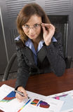Graph brunette. Young attractive businesswoman looking at graphs in a modern office setting Royalty Free Stock Photo