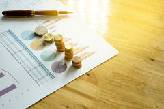 Graph chart on the paper and gold coin Stock Image