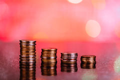 Graph with coins: red losses. Stacks of coins showing a decrease on a red background with selective focus royalty free stock image