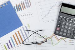 Graph with notebook, glasses and calculator on stock market report as background royalty free stock photos