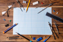 Graph paper with copyspace and student material on wooden table. Stock Photo