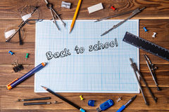 Graph paper with text - back to school and student material on wooden table. Stock Photos