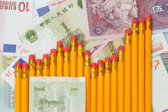 Graph of pencils against background of yuan and euro banknotes Royalty Free Stock Photo