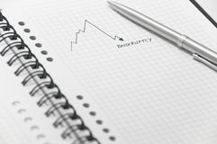 Graph pointing to bankruptcy on spiral notebook. Graph pointing to bankruptcy on white spiral notebook with elegant silver pen Stock Photos