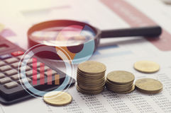 Graph,row of money coisn , calculator and magnifier on paper  finance Stock Photography