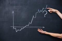 Graph showing uncertainty drawn on blackboard. Decreasing and increasing graph showing uncertainty drawn on blackboard background Stock Image