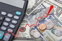Graph showing USD bank notes with coins and a calculator. Graph showing economy strengthening of United States bank notes and coins with a calculator Royalty Free Stock Images