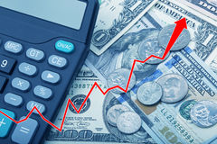 Graph showing USD bank notes with coins and a calculator. Graph showing economy strengthening of United States bank notes and coins with a calculator Stock Photography