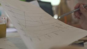 Female drawing on a graph. The graph on white paper is fixing with a silver pen. Than another chart is correcting too. Close-up stock video footage