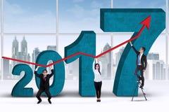 Grapha della tenuta di tre lavoratori con il numero 2017 Immagine Stock