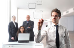 Graphic. Young businessman drawing a graphic with group of business people on the background Royalty Free Stock Image
