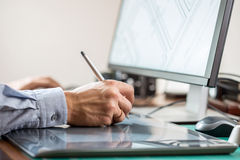 Graphic artist using graphics tablet. At his desk Stock Photography