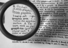 Graphic-Arts. Photo of Dictionary and Magnifying Glass Emphasizing Graphic Arts stock images