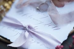 Lilac silk ribbon. Graphic arts of beautiful wedding calligraphy cards with flower and chiffon bobbins on wood background. Beautiful wedding invitation. Details Stock Photos